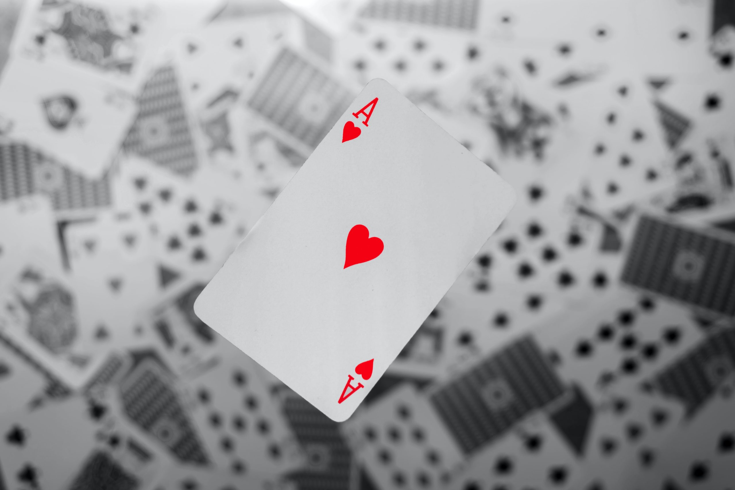 Close up of a playing card with the ace of hearts floating above the rest of the cards scattered below.