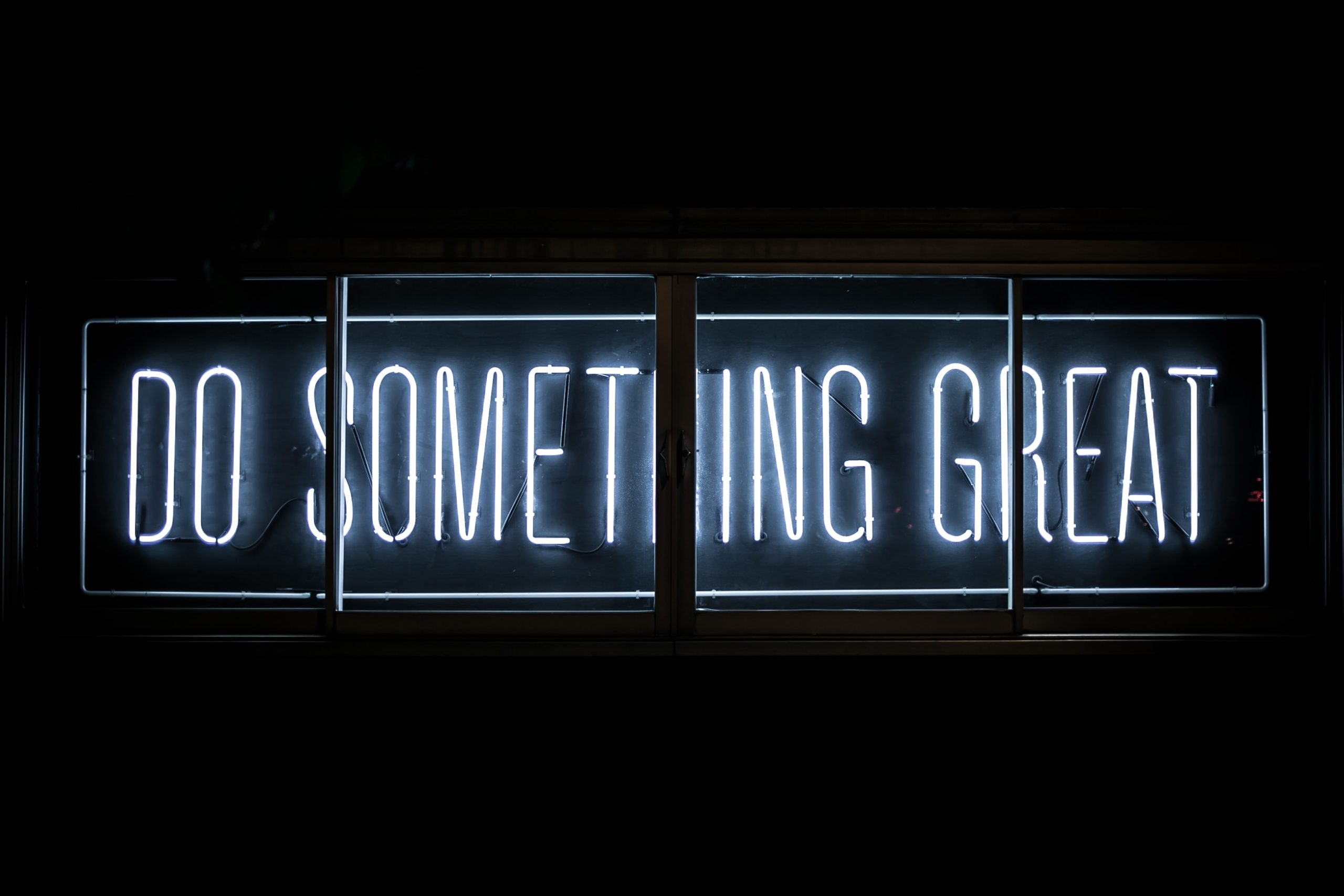 Close up of a white neon sign saying do something great on a black wall.