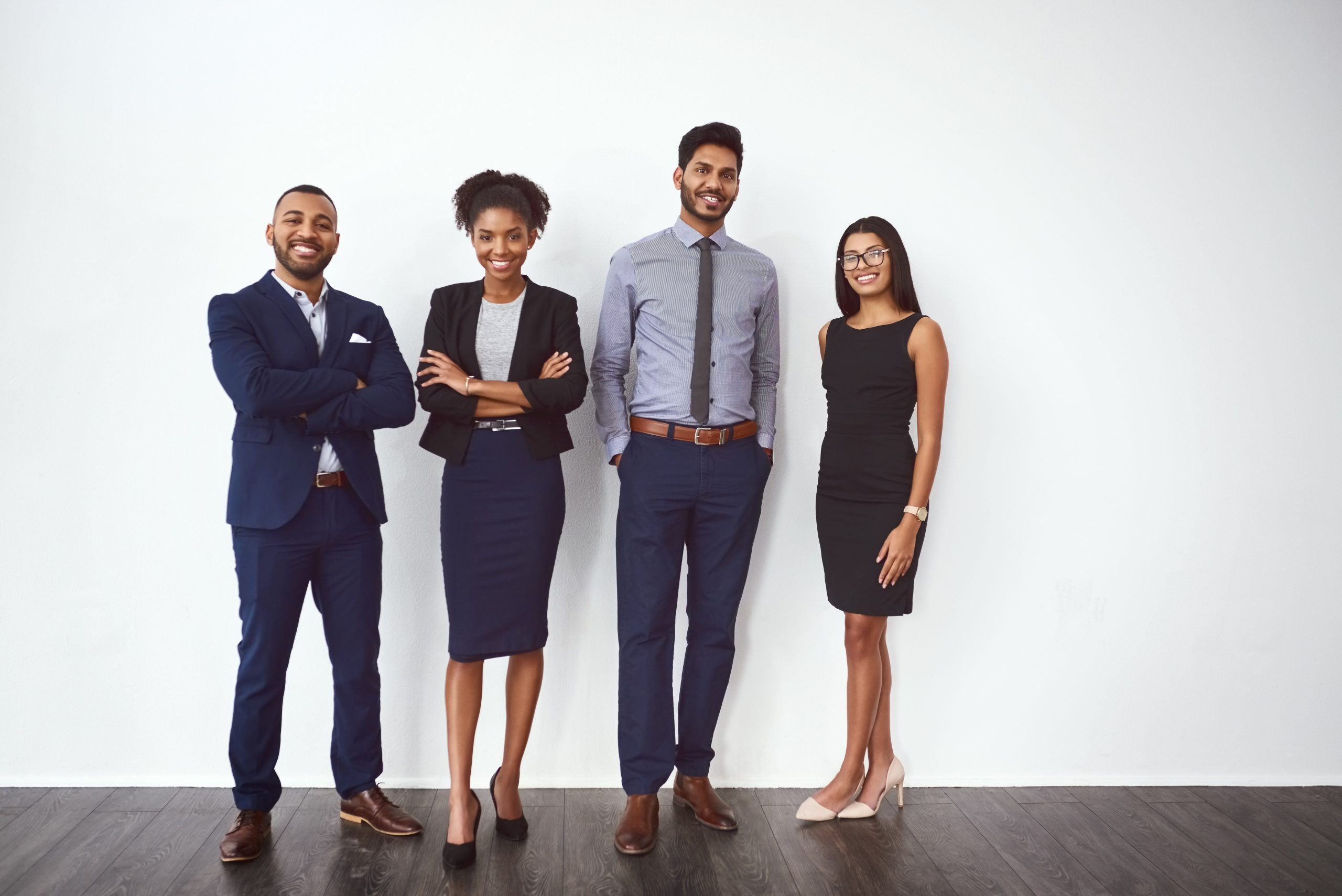 Studio portrait of a group of confident young businesspeople posing against a gray background