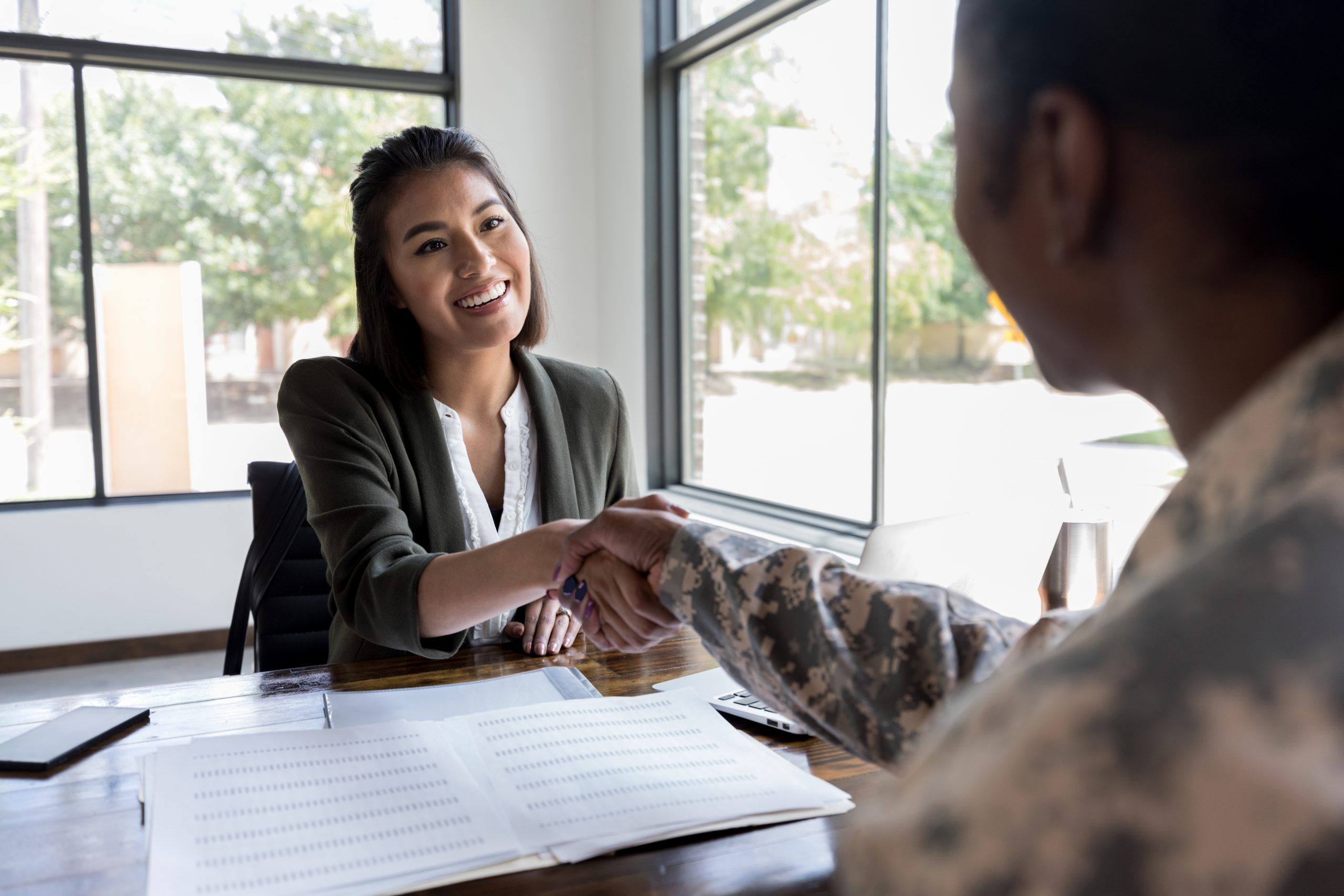 Smiling young female financial advisor greets female soldier.