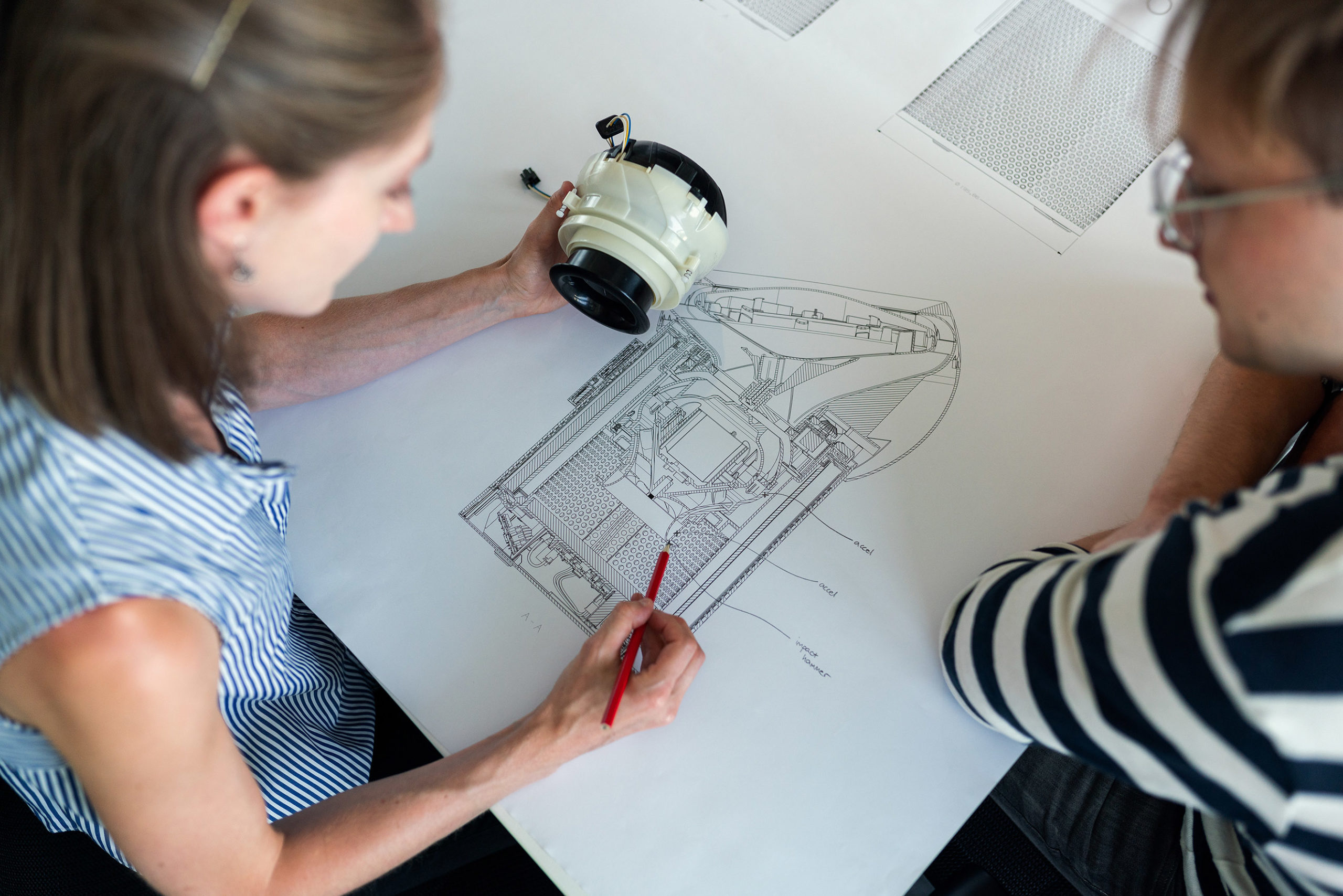 One employee drawing a diagram of a piece of equipment that she is holding in her hand while another is sitting on the side looking at the drawing.